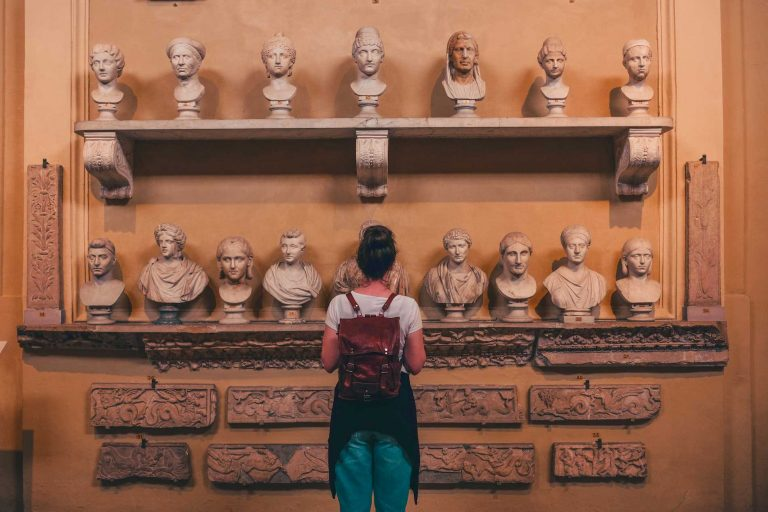 Girl in front of Roman statues at Vatican Museums during a tour with Rome for kids